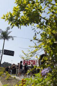 manifestantes caminham com faixa com os dizeres 'Basta! Queremos um lugar seguro pra viver'; foto tirada através de ramos de uma moita