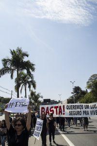 manifestantes caminham com faixa com os dizeres 'Basta! Queremos um lugar seguro pra viver'; uma manifestante também segura um cartaz escrito '#paz'