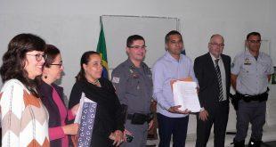 duas representantes do movimento responsável pelo abaixo-assinado, Goreti, Fernandes, Almir, Marcos e Ricardo posam para foto; o documento está nas mãos de Almir