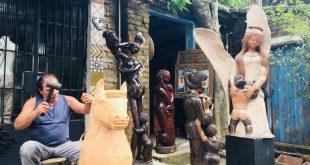 claudio veneranto esculpindo uma escultura em madeira, com diversas obras à sua volta