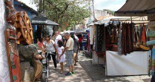 foto da Feira de Embu das Artes, com diversas bancas com produtos expostos e frequentadores caminhando em meio a elas