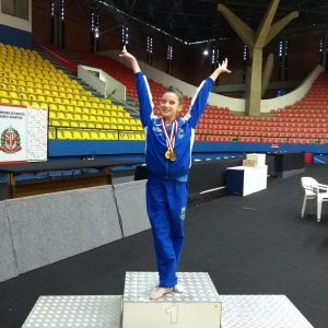 ginasta posa no primeiro lugar do pódio