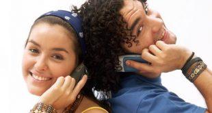 um homem e uma mulher de costas um para o outro, encostados, olhando para a câmera e falando ao celular