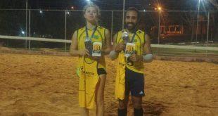 Gabriela e Marcos, a dupla campeã do 1º Torneio Misto de Vôlei de areia noturno, posa com medalhas