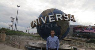 marcos paes de barros posa diante de uma escultura do globo da universal no complexo da marca em Orlando