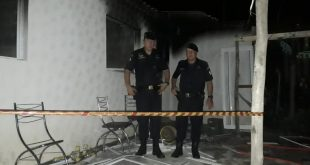 dois guardas civis posam dentro de casa incendiada