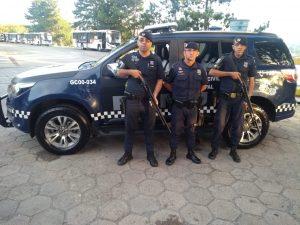 três guardas da ROMU posam diante de viatura
