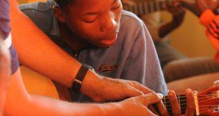 aluno recebendo instruções sobre como tocar o violão