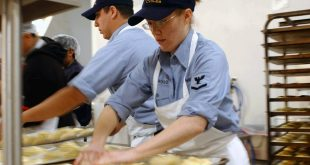 dois aprendizes preparando pães