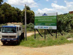 um caminhão estacionado ao lado da placa informativa referente à obra de pavimentação da Rua Antônio Meleiro