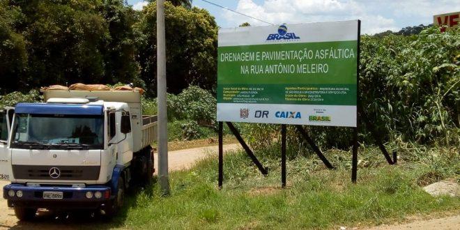 um caminhão estacionado ao lado da placa informativa referente à obra
