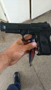 Réplica arma de fogo sendo segurada pela mão de um guarda civil