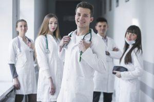 uma equipe médica sorri para a câmera no corredor de uma unidade de saúde
