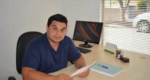 vereador rafael tanzi posa para foto sentado na mesa de seu gabinete
