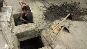 homens limpando boca de lobo na Rua Ciro Monteiro