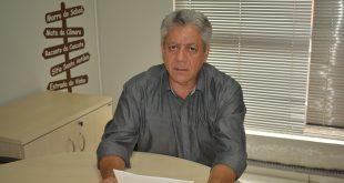 vereador josé luiz posa sentado a uma mesa com documentos em mãos