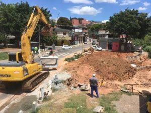 retroescavadeira trabalhando em grande buraco com bairro ao fundo