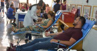 edson silva e uma munícipe na cadeira de doação, com dezenas de outros participantes ao fundo