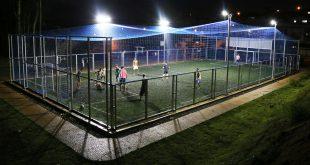 foto noturna da quadra de futebol society do jardim vargem grande com os refletores ligados e iluminando o local enquanto atletas disputam uma partida