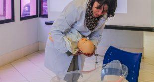 médica manipulando boneca em palestra sobre gravidez de alto risco