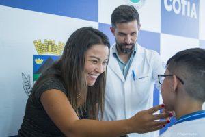 primeira dama mara franco coloca óculos em criança observada pelo secretário de saúde Magno Sauter