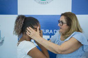 secretária de educação neusa abreu coloca óculos em criança