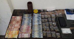 dinheiro, drogas e documentos dispostos em uma mesa