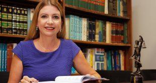 a advogada Marília Valença, do Ateliê do Direito, sorri para a câmera sentada a uma mesa e manuseando um livroem frente a uma estante cheia de outros títulos