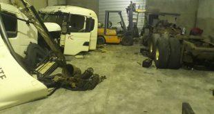 interior do desmanche, com várias peças de caminhões empilhadas