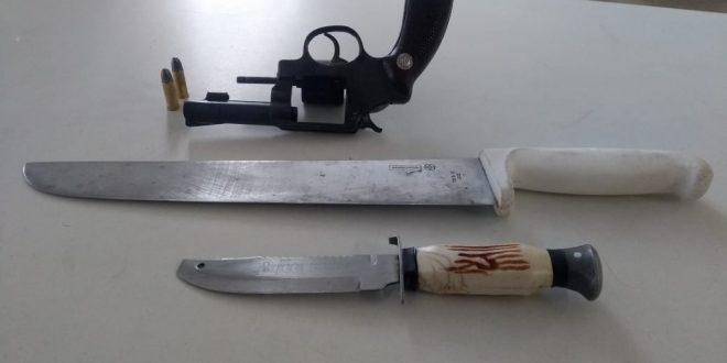 um revólver e duas facas dispostos sobre uma mesa
