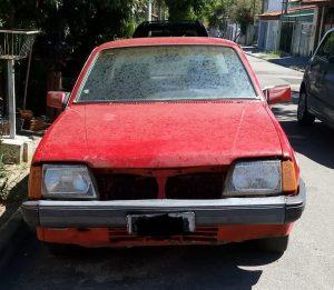vista frontal de carro antigo que foi roubado e depois abandonado