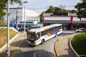 um ônibus de cotia visto de um viaduto, dobrando uma esquina e prestes a descer uma ladeira que passará embaixo da ponte