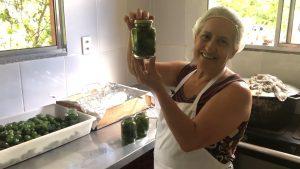 uma senhora exibe um alimento produzido por ela, dentro de um pote