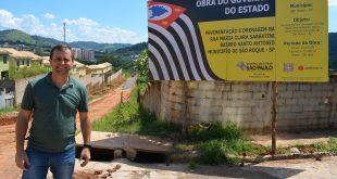 vereador cabo jean posa ao lado de placa informativa da obra de asfaltamento