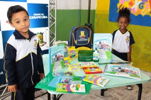 dois alunos posam ao lado de mesa com novos materiais