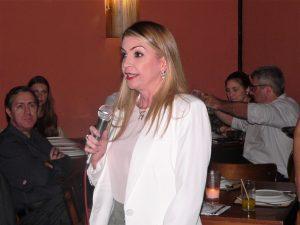 Marília Valença com um microfone em mãos discursando