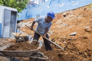 homem trabalhando em obra do muro