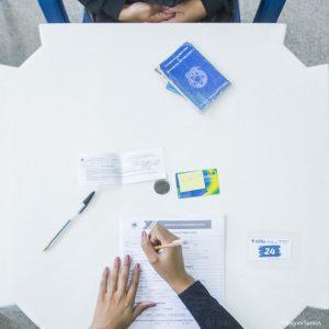 vista de cima de uma mesa com um par de mãos trabalhando em um formulário com uma carteira de trabalho ao lado