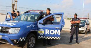 uma viatura da romu da guarda civil de carapicuíba com quatro guardas posando em volta com uma viatura da guarda ao fundo