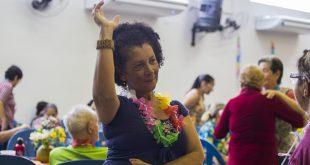 uma idosa com um colar de flores havaiano dançando num baile da terceira idade de cotia