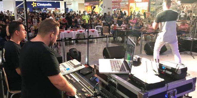 um cantor se apresentando num palco no plaza shopping carapicuíba com um operador de audiovisual ao lado e o público ao fundo