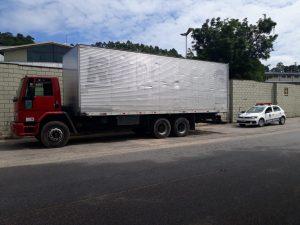 vista lateral de um caminhão baú de cabine vermelha da marca Ford estacionado com uma viatura da GCm logo atrás