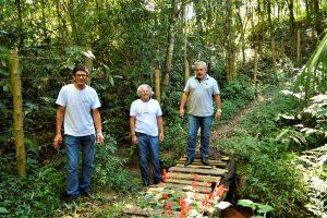julio mariano e duas outras pessoas posam em meio a bosque