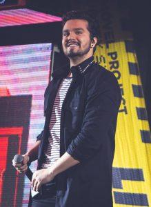 luan santana sorri no palco com um microfone em mãos