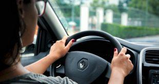 vista traseira direita de uma mulher conduzindo um veículo da marca renault