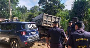 guardas e viaturas estacionadas perto de caminhão descarregando entulho