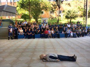 boneco deitado em um pátio com dezenas de alunos observando ao fundo