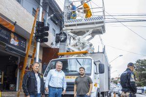 um agente de trânsito, o secretário joaquim brechó e o engenheiro fernando posam para foto diante de caminhão que trabalha na instalação do semáforo