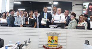 padre José Maria Falco, vereadores e autoridades posam com homenagem em mãos