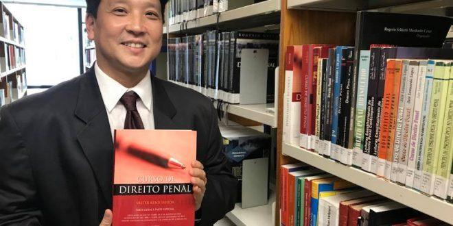 Valter Ishida posa para foto com um livro de direito penal em mãos